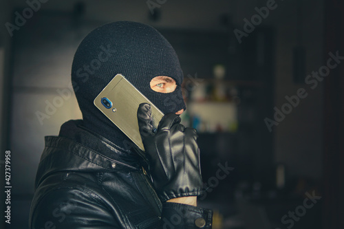 Fototapeta Young adult in black clothes with hidden face