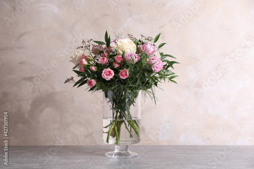 Obraz Beautiful bouquet with roses on table against grey background - fototapety do salonu
