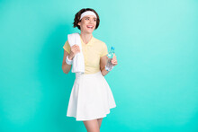 Photo Of Cheerful Nice Young Positive Woman Look Empty Space Dream Hold Towel Water Bottle Isolated On Teal Color Background