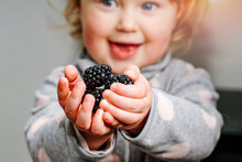 A Little Girl Holds Fresh Blackberries In Her Hands With A Smile On Her Face.