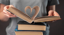 Female Hands Of Book Lover Holding Textbook With Heart-shaped Pages