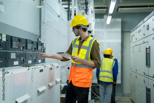 Obraz Engineer working on works on a tablet computer in switchgear room of a modern thermal power plant at large industry factory. - fototapety do salonu