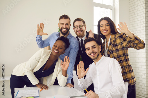 Group portrait of happy multicultural office workers waving hands at camera and smiling. Webcam video chat or teleconference view of team of young mixed race business people saying hello to colleagues