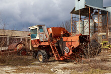 Devastation And Decline In The Agro-industrial Sector. Cemetery Of Old Rusty Agricultural Machinery. Industrial Area.