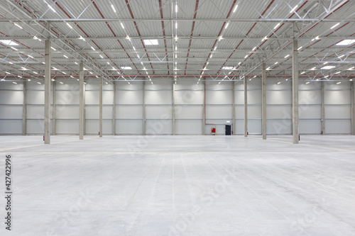 Leere Wand mit Notausgang und Feuerlöscher in neuer und leerer Halle mit viel Fläche und Flucht #427422996