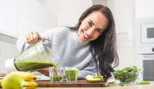 Similing Female Pours Freshly Made Green Smoothie Into Glasses In The Kitchen
