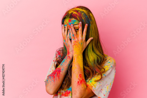 Foto Young Indian woman celebrating holy festival isolated on white background blink through fingers frightened and nervous