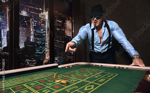 Tableau sur Toile brutal athletic man dressed in suit with a cigar plays in a casino