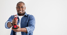 Black Handyman Holding Screwdriver Like Gun And Aiming At Camera, Isolated On White Background, Panorama With Copy Space