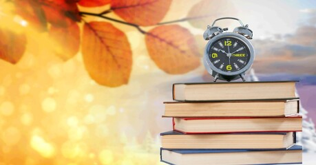 Alarm clock on a stack of books against autumn and winter landscapes