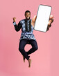 canvas print picture Check this out, cellphone display mockup. Excited black man showing smartphone with empty screen on pink background