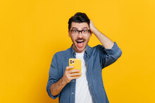 Amazed Shocked Positive Caucasian Guy With Glasses, Uses Smartphone, Browsing Internet, Social Networks, Get Unexpected News, Holding His Head With His Hand, Stands On Isolated Orange Background