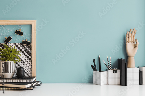 Desk with a drawing supplies, note, desk objects, pencils, brushes, and plant near bright pastel wall. - fototapety na wymiar