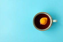 Yellow Rubber Duck Swimming Into Cup Of Tea On Blue Background. Creative Summer Vacation Concept. Top View