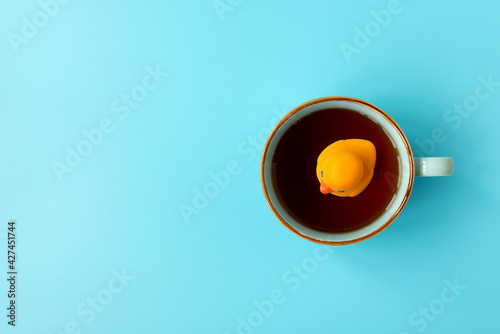 Fotografie, Obraz Yellow rubber duck swimming into cup of tea on blue background