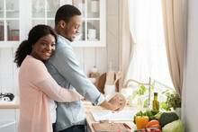 Grateful African Wife Cuddling Husband From The Back While He Washing Dishes