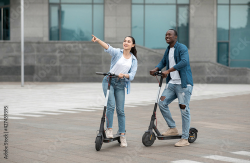 Woman pointing at view, using electric scooter outdoor