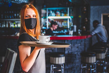 Portrait Young Waitress Standing In Cafe. Girl The Waiter Holds In Bunches A Tray With Utensils. Restaurant Service