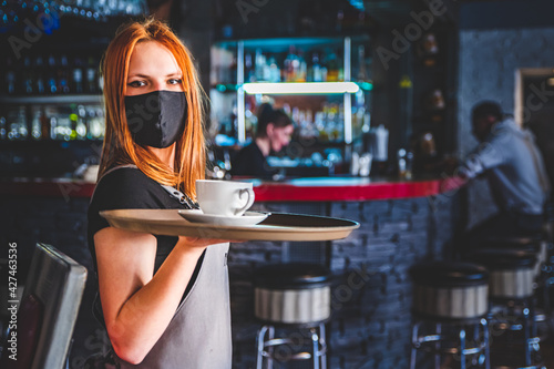 Obraz Portrait young waitress standing in cafe. girl the waiter holds in bunches a tray with utensils. Restaurant service - fototapety do salonu