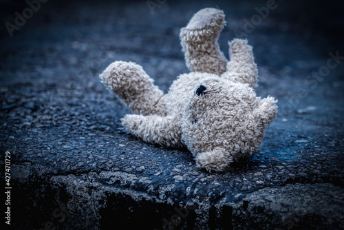 Lost childhood concept. Dirty teddy bear lying down outdoors.