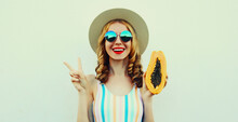 Summer Portrait Of Happy Smiling Young Woman With Papaya Wearing A Straw Hat, Sunglasses On A White Background