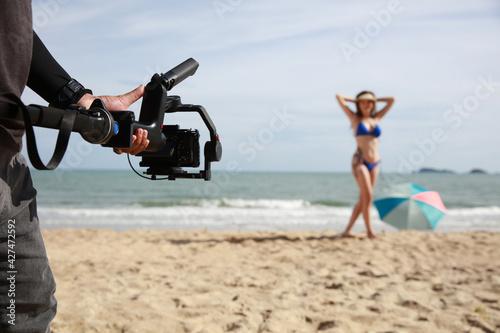 Professional Photographer and film maker shoot video sexy woman with bikini on b Fototapet