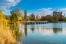 Germany, Freiburg Im Breisgau City Park Seepark Lake Water Swimming Bridge Surrounded By Gree Nature Landscape And Houses