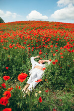 Young Pretty Woman Laying Down At The Field Of Poppy Flowers