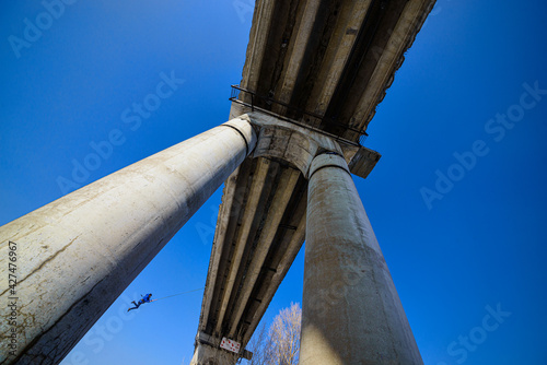 Fototapeta premium bottom view of man jumping from high bridge on sky background at sunny day