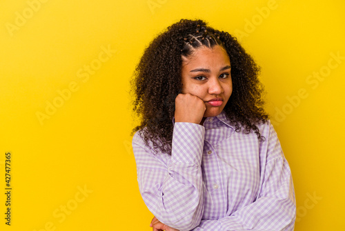 Obraz na plátne Young african american woman isolated on yellow background who feels sad and pensive, looking at copy space