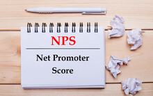 On A Wooden Background, A White Notebook With The Inscription NPS Net Promoter Score, A White Pen And Crumpled White Pieces Of Paper