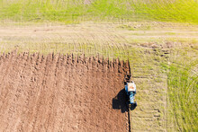 Top Aerial View Of Tractor Plowing Ground On Agriculture Farm Field.