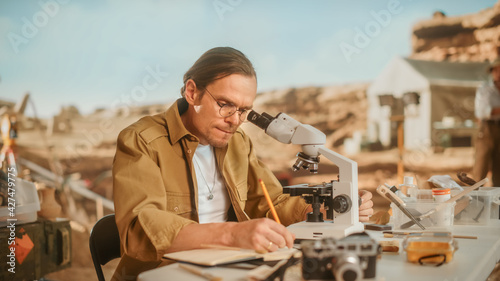 Archaeological Digging Site: Male Archeologist Doing Indigenous Culture Research, Discovers Ancient Civilization Historical Artifacts, Fossil Remains at Excavation Site, Study it Under Microscope - fototapety na wymiar