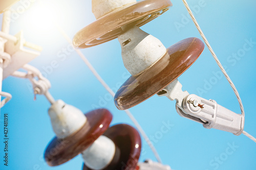 Fotografie, Obraz A ceramic suspended insulator hangs from a power line against a blue sky