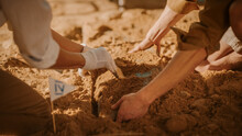 Archaeological Digging Site: Two Great Archeologists Work On Excavation Site, Carefully Cleaning, Lifting Newly Discovered Ancient Civilization Cultural Artifact, Historic Clay Tablet. Focus On Hands