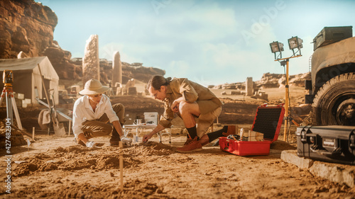 Fotografija Archaeological Digging Site: Two Great Archeologists Work on Excavation Site, Cleaning Cultural Artifacts with Brush and Tools