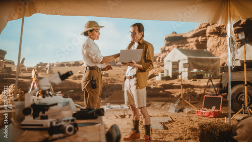 Fotografija Archaeological Digging Site: Two Great Archeologists Stand in Tent Work on Excav