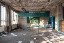 Abandoned Classroom In Soft Tones, View Of Chalkboard And Chaos Of Papers