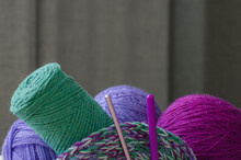 Multi-colored Yarn For Knitting And Hooks On A Gray Background