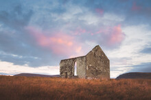 Old, Ancient Stone Ruins Of The Remote And Isolated Kilmuir Church In The Scottish Rural Countryside Under A Vibrant, Colourful Sunset Or Sunrise Sky On The Isle Of Skye, Scotland.