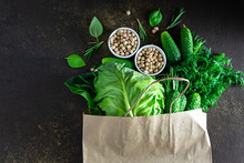 Set Of Organic Fresh Green Vegetables In Reusable Paper Bag On Dark Rustic Background. Farmer's Market Banner Concept. Eco Food Delivery Background.