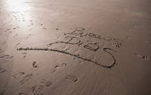 At Dawn On The Beach Written On The Wet Sand A Good Morning Message, Traces Of People Can Be Seen.
