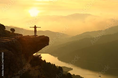 Slika na platnu Woman celebrating in a beautiful sunset landscape