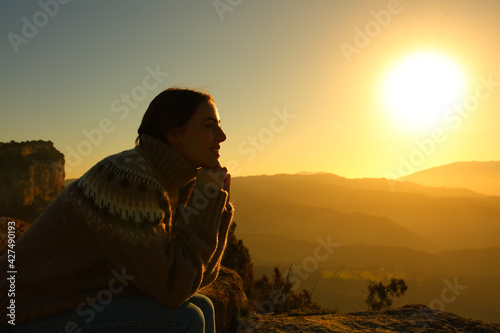 Woman silhouette meditating at sunset in the mountain - fototapety na wymiar