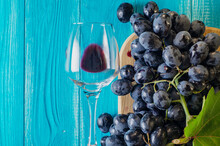Black Grapes And Wine Glass On A Blue Wooden Table, Top View.