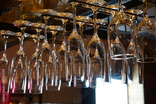 Obraz na plátně Clean  Champagne Glasses hanging from copper pipe rack in bar - シャンパン グラス