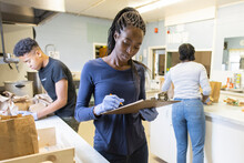 Young Female Volunteer With Clipboard In Community Center Kitchen