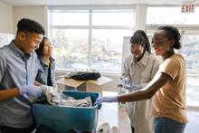 Teenage Volunteers Sorting Clothing Donations In Community Center