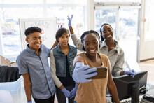 Happy Teenage Volunteers Taking Selfie In Community Center
