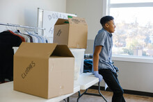 Teenage Boy Volunteering At Clothing Drive In Community Center